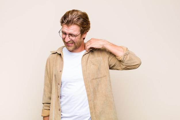 Blonder erwachsener mann, der sich gestresst, ängstlich, müde und frustriert fühlt, hemdhals zieht und mit problem frustriert aussieht