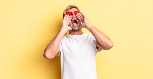 Blonder erwachsener mann, der sich glücklich fühlt, mit den händen neben dem mund einen großen schrei ausspricht und eine sonnenbrille trägt