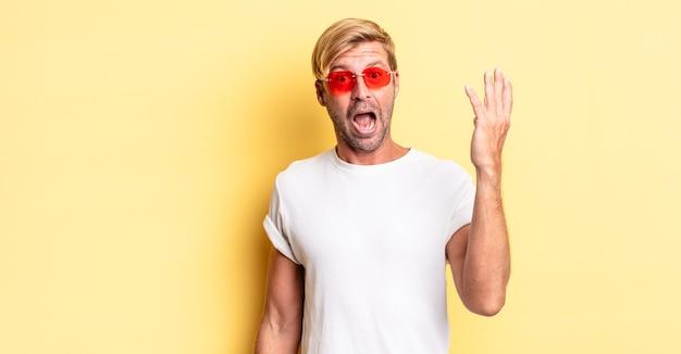 Blonder erwachsener mann, der sich glücklich fühlt, überrascht, eine lösung oder idee zu erkennen und eine sonnenbrille zu tragen