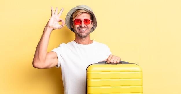 Blonder erwachsener mann, der sich glücklich fühlt und zustimmung mit okayer geste zeigt. reisende-konzept