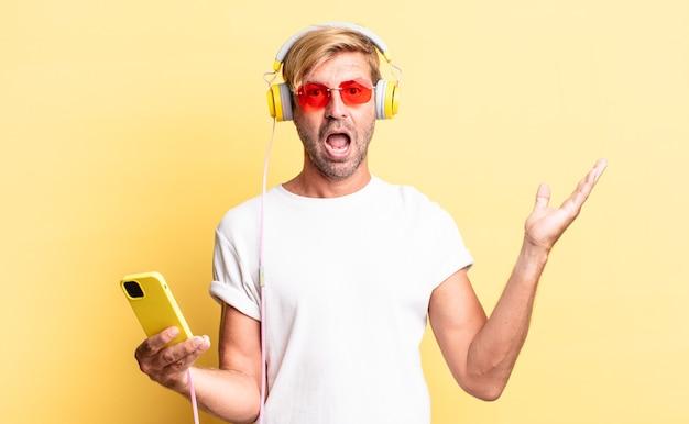Blonder erwachsener mann, der sich glücklich und erstaunt über etwas unglaubliches mit kopfhörern fühlt