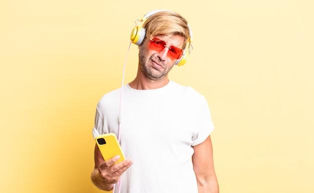 Blonder erwachsener mann, der sich mit kopfhörern verwirrt und verwirrt fühlt