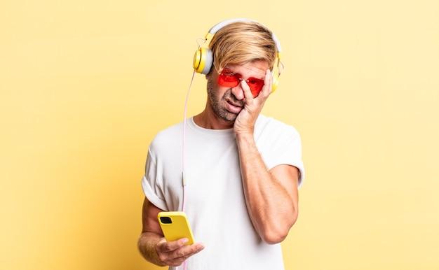 Blonder erwachsener mann, der sich nach einem lästigen kopfhörer mit kopfhörern gelangweilt, frustriert und schläfrig fühlt