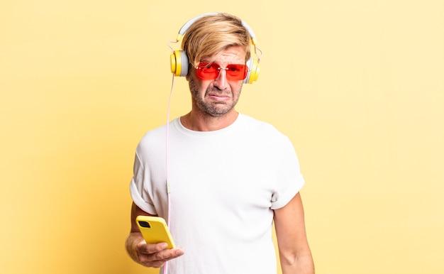 Blonder erwachsener mann, der sich traurig und weinerlich mit einem unglücklichen blick fühlt und mit kopfhörern weint