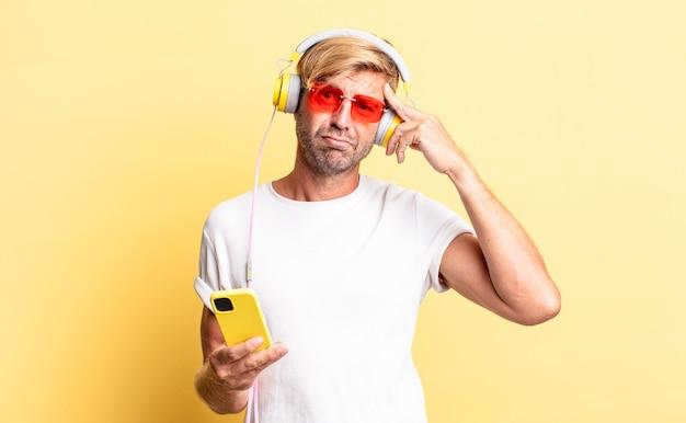 Blonder erwachsener mann, der sich verwirrt und verwirrt fühlt und zeigt, dass sie mit kopfhörern verrückt sind