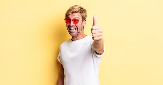 Blonder erwachsener mann, der stolz ist, positiv mit daumen nach oben lächelt und eine sonnenbrille trägt