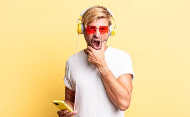 Blonder erwachsener mann mit weit geöffnetem mund und augen und hand am kinn mit kopfhörern
