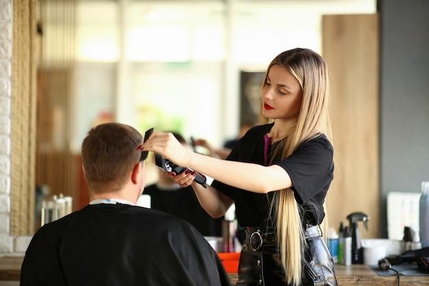 Blonder friseur shaving man durch elektrorasierer. frauen-herrenfriseur using shaver und haarbürste für das anreden des männlichen haarschnitts