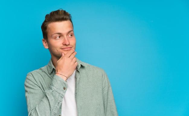 Blonder gutaussehender mann mit grünem hemd eine idee denkend