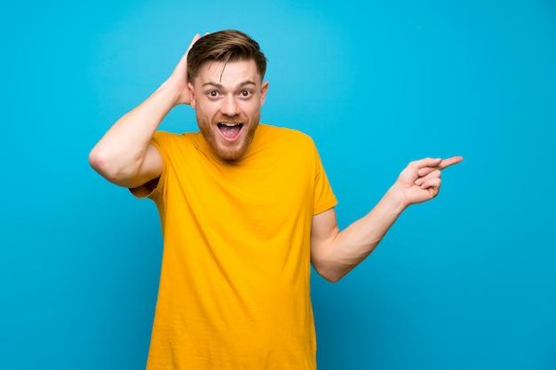 Blonder gutaussehender mann mit grünem hemd zeigend mit dem zeigefinger eine großartige idee