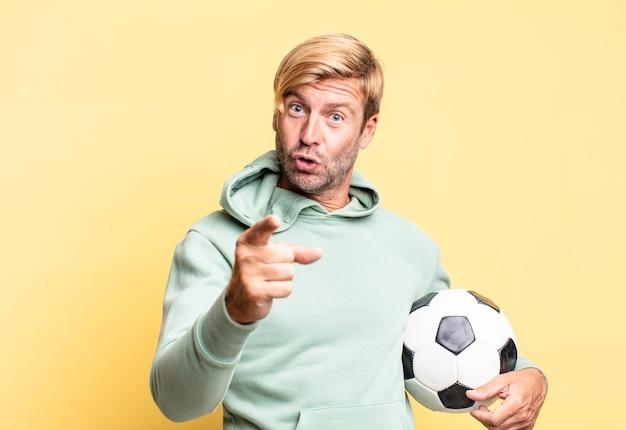 Blonder hübscher erwachsener mann, der einen fußball hält