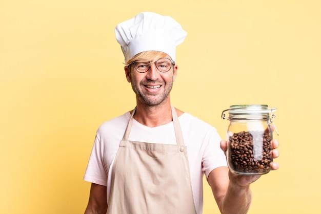 Blonder hübscher erwachsener mann des chefkochs, der eine kaffeebohnenflasche hält