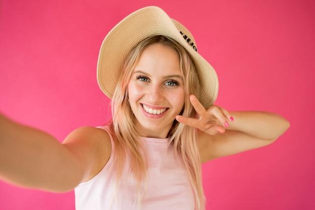 Blonder influencer, der ein selfie nimmt