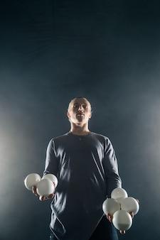 Blonder jongleur mit weißen bällen auf schwarzem hintergrund