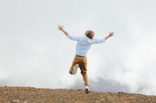 Blonder junge, der auf wunderbare ansicht des bergurlaubsorts springt