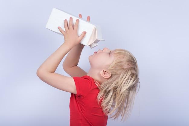 Blonder junge, der milch aus karton trinkt
