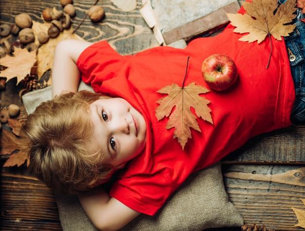 Blonder junge, der mit einem apfel auf bauch ruht, liegt auf holzboden im herbstlaub. die größten rabatte für alle herbstkleidung für kinder. kind spielt im herbst.