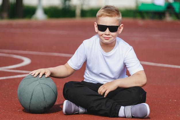 Blonder junge, der mit einem basketballball auf dem spielplatz sitzt. foto in hoher qualität