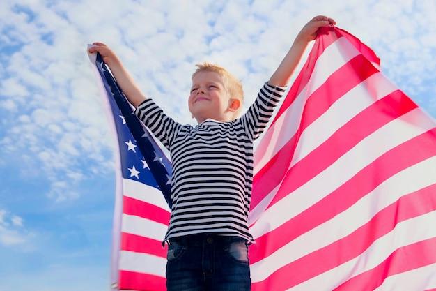 Blonder junge, der nationale usaflagge im freien über blauem himmel im sommer winkt