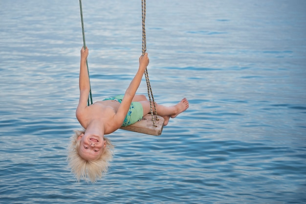 Blonder junge, der schaukel über dem meer reitet