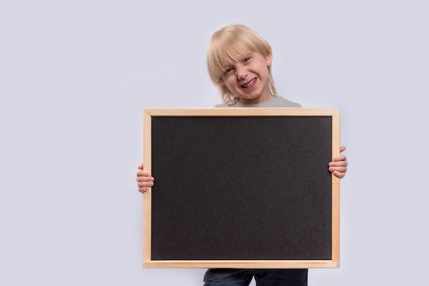 Blonder junge, der tafel hält und lächelt. speicherplatz kopieren. vorlage. attrappe, lehrmodell, simulation.