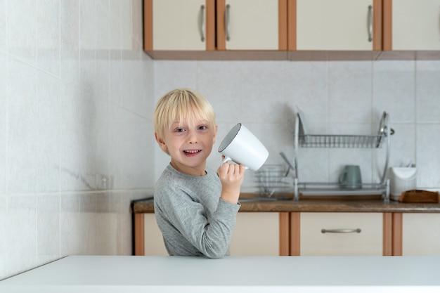 Blonder junge, der von der großen tasse in der küche trinkt. lustiges schuljungenfrühstück.
