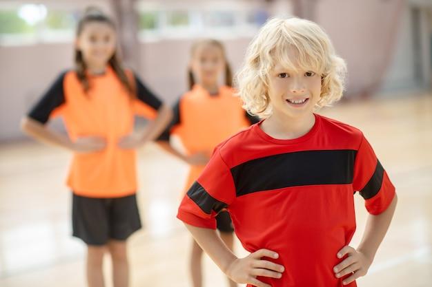 Blonder junge im roten t-shirt stehend mit den händen auf den hüften