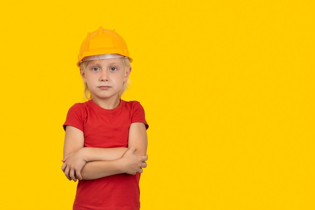 Blonder junge im schutzhelm auf gelbem hintergrund. wahl des zukünftigen berufs.