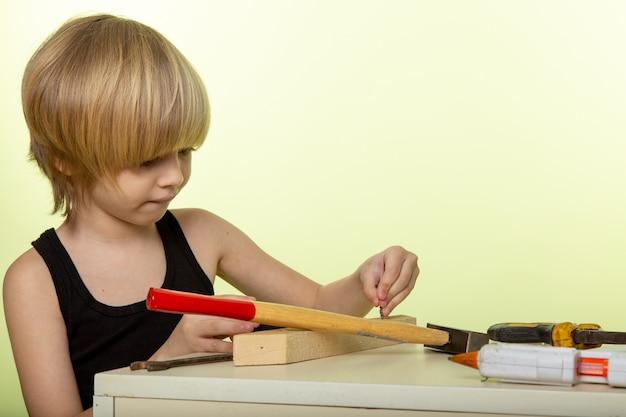 Blonder junge im schwarzen t-shirt, das mit hammer und anderen werkzeugen auf weißer wand arbeitet