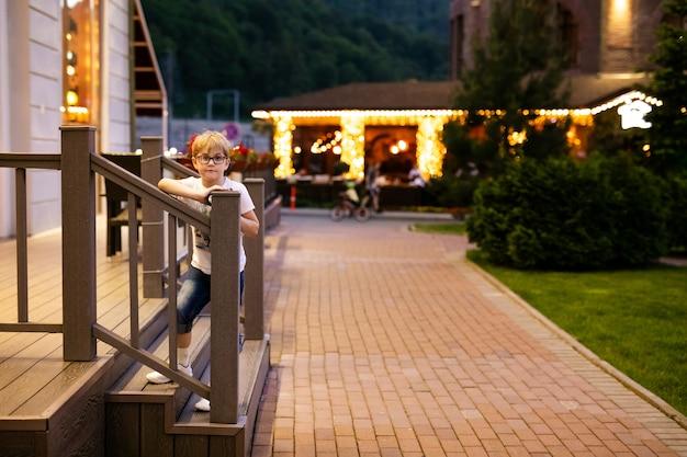 Blonder junge in den großen gläsern draußen am abend gehend