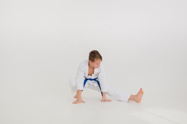 Blonder junge in einem weißen kimono mit einem blauen gürtel macht eine strecke an einer weißen wand