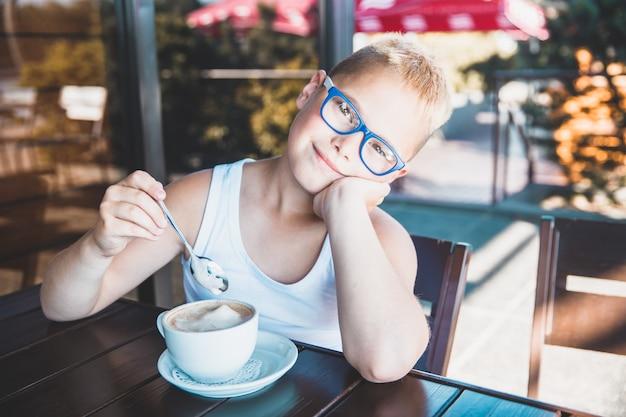 Blonder junge in einem weißen t-shirt in einem restaurant, das kaffee trinkt