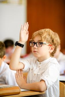 Blonder junge mit den großen schwarzen gläsern, die im klassenzimmer, studierend sitzen und lächeln. grundschulunterricht, erster schultag