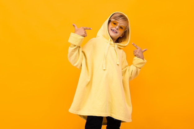 Blonder junge mit einem panama in einem hellen kapuzenpulli mit brille auf orange