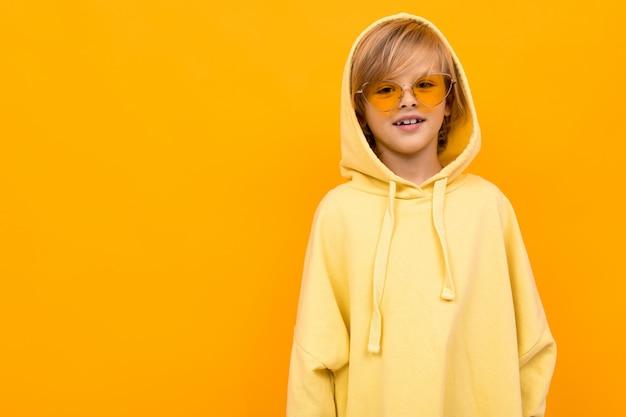Blonder junge mit einem panama in einem hellen kapuzenpulli mit brille, die auf gelbem studio aufwirft