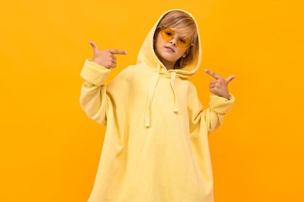 Blonder junge mit einem panama in einem hellen kapuzenpulli mit brille, die auf orange studio aufwirft