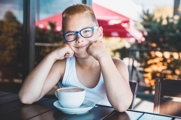 Blonder junge mit gläsern in einem restaurant, das kaffee trinkt