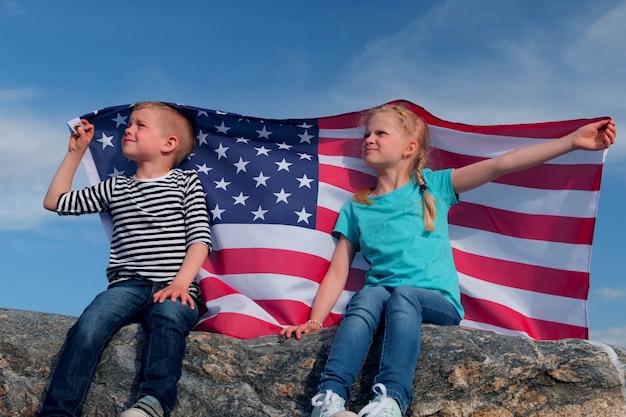 Blonder junge und mädchen, die nationale usaflagge im freien über blauem himmel im sommer winken