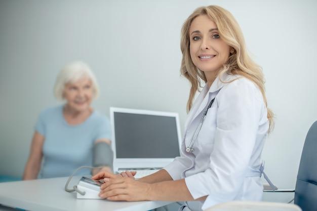 Blonder junger arzt, der einen älteren patienten konsultiert
