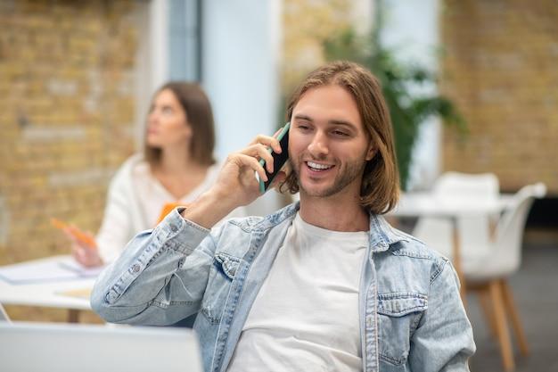 Blonder junger mann, der am laptop sitzt und am telefon spricht