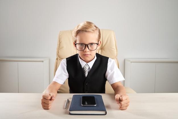 Blonder kaukasischer junge, der am schreibtisch im büro sitzt und chef spielt