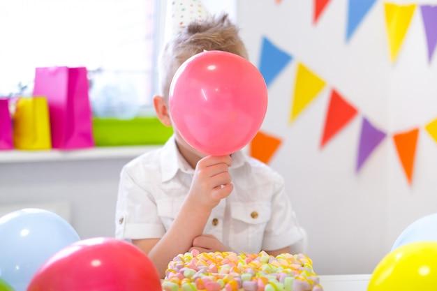 Blonder kaukasischer junge versteckte sich hinter einem roten ballon nahe geburtstagsregenbogenkuchen. festlicher bunter hintergrund. lustige geburtstagsfeier