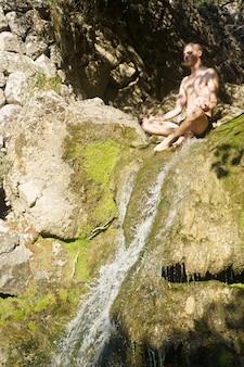 Blonder kaukasischer mann, der an der spitze eines wasserfalls mit nacktem oberkörper meditiert. palma de mallorca, spanien