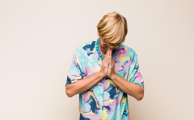 Blonder kerl, der sich besorgt, hoffnungsvoll und religiös fühlt