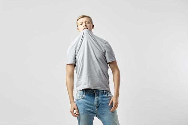 Blonder kerl in einem weißen t-shirt und jeans steht auf dem weißen hintergrund