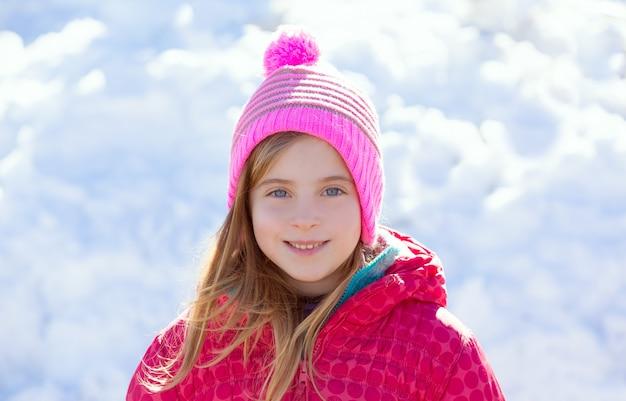 Blonder kindermädchen-winterhut im schneelächeln