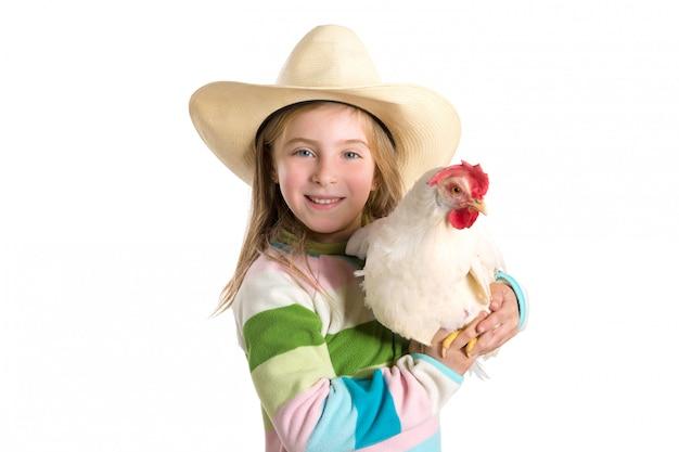 Blonder kindermädchenlandwirt, der weiße henne auf armen hält