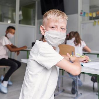 Blonder kleiner junge, der eine medizinische maske trägt