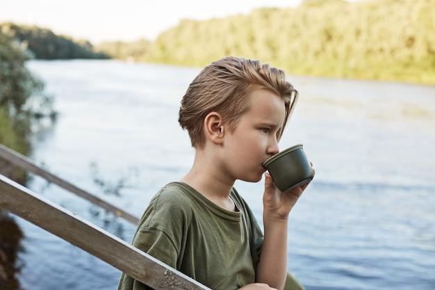 Blonder kleiner junge, der heißen kaffee von der thermoskanne trinkt