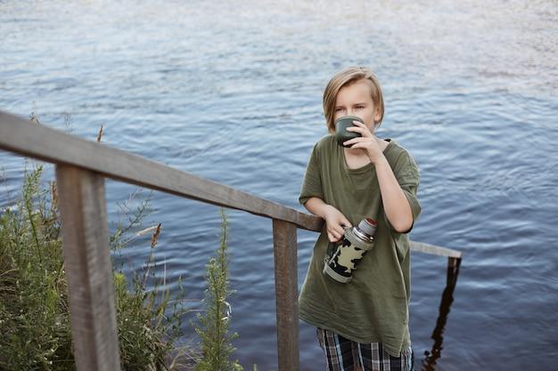 Blonder kleiner junge, der heißen tee von der thermoskanne isoliert über fluss trinkt, männliches kind, das zeit im freien verbringt, grünes t-shirt trägt, heißes getränk genießt, während nahe wasser aufwirft.